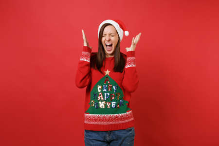 Crazy Santa girl with closed eyes in knitted sweater, Christmas hat screaming, spreading hands isolated on red background. Happy New Year 2019 celebration holiday party concept. Mock up copy space