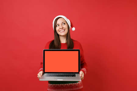 Dreamy young Santa girl looking up holding laptop pc computer with blank empty screen isolated on bright red wall background. Happy New Year 2019 celebration holiday party concept. Mock up copy space