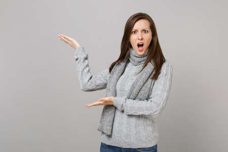 Irritated shocked young woman in gray sweater scarf swearing pointing hands aside isolated on grey wall background. Healthy fashion lifestyle, people emotions, cold season concept. Mock up copy space