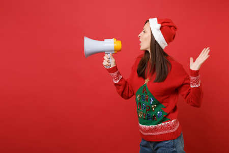 Side view of young Santa girl in knitted sweater, Christmas hat holding megaphone spreading hands isolated on red background. Happy New Year 2019 celebration holiday party concept. Mock up copy space