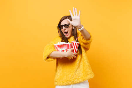Scared woman in 3d imax glasses screaming trying to closing screen by palm watching movie film holding popcorn cup of cola isolated on yellow background. People sincere emotions in cinema, lifestyle