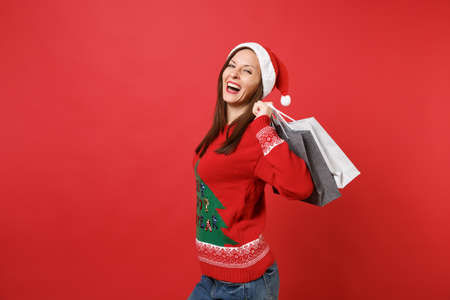Laughing pretty young Santa girl holding packages bags with purchases after shopping isolated on bright red wall background. Happy New Year 2019 celebration holiday party concept. Mock up copy space