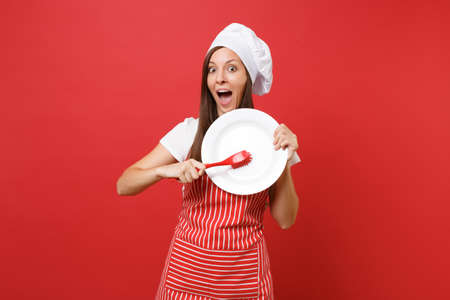 Housewife female chef cook or baker in striped apron, white t-shirt, toque chefs hat isolated on red wall background. Woman hold white plate with brush for washing dishes. Mock up copy space concept