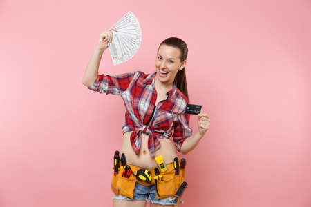 Handyman woman in plaid shirt denim shorts, kit tools belt full of variety instruments hold lots of cash dollar money, credit card isolated on pink background. Female in male work. Renovation concept 写真素材