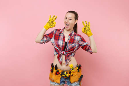 Happy handyman woman in shirt, denim shorts, yellow gloves, kit tools belt full of variety useful instruments showing OK gesture isolated on pink background. Female in male work. Renovation concept