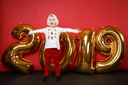 Merry Santa boy in Christmas hat celebrating holiday party isolated on bright red wall background, golden shiny glitter numbers air balloons, full length studio portrait. Happy New Year 2019 concept Stock Photo