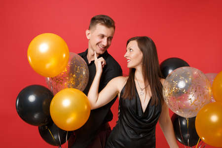 Stunning young couple in black clothes celebrating birthday holiday party isolated on bright red background air balloons. St. Valentine's International Women's Day Happy New Year 2019 concept. Banco de Imagens