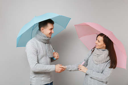 Couple girl guy in gray sweaters scarves together under umbrella isolated on grey wall background, studio portrait. Healthy lifestyle sick disease treatment cold season concept. Mock up copy space