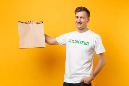 Portrait of man in white t-shirt written inscription green title volunteer hold blank craft paper bag for takeaway isolated on yellow background. Voluntary free assistance help charity grace concept