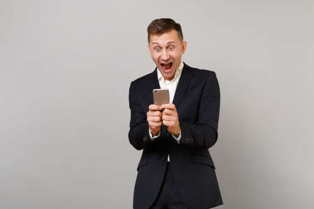 Surprised happy young business man screaming keeping mouth open wide, using mobile phone typing sms message isolated on grey background. Achievement career wealth business concept. Mock up copy space Stock fotó