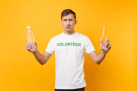 Disgusted man in t-shirt volunteer hold plastic glass bottles isolated on yellow background. Voluntary free help. Environmental pollution problem. Stop nature garbage environment protection concept