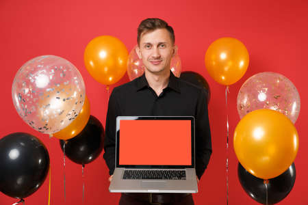 Handsome young man in black classic shirt holding laptop pc computer with blank black empty screen on red background air balloons. Valentine's Day Happy New Year birthday mockup holiday party concept