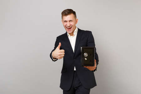 Laughing young business man in classic suit showing thumb up holding metal bank safe for money accumulation isolated on grey background. Achievement career wealth business concept. Mock up copy space 版權商用圖片