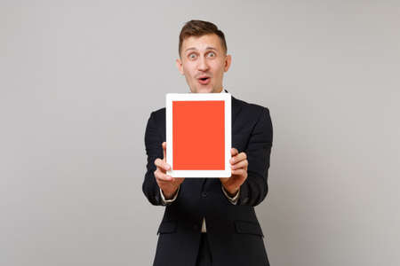 Surprised young business man in classic black suit shirt holding tablet pc computer with blank empty screen isolated on grey background. Achievement career wealth business concept. Mock up copy space Stock Photo