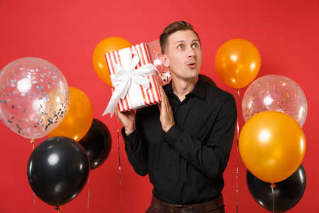 Amazed young man in black classic shirt holding red box with gift, present on bright red background air balloons. St. Valentine's, Women's Day, Happy New Year, birthday mockup holiday party concept Banco de Imagens