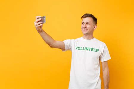 Retrato de hombre en camiseta blanca escrito voluntario de título verde inscripción tomando selfie tiro en teléfono móvil aislado sobre fondo amarillo. Asistencia gratuita voluntaria ayuda concepto de trabajo de gracia de caridad