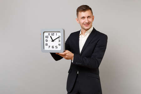 Portrait of handsome young business man in classic black suit and shirt holding square clock isolated on grey wall background in studio. Achievement career wealth business concept. Mock up copy space