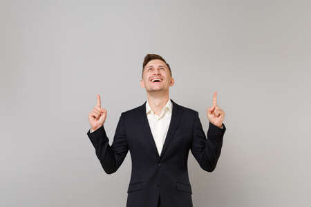 Smiling young business man in classic black suit, white shirt looking, pointing index fingers up isolated on grey background in studio. Achievement career wealth business concept. Mock up copy space