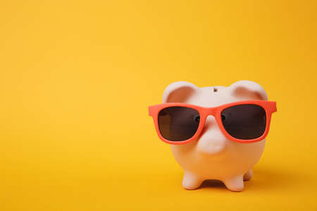 Close up photo of pink piggy money bank with sunglasses isolated on yellow wall background. Money accumulation investment, banking or business services, wealth concept. Copy space advertising mock up Banco de Imagens
