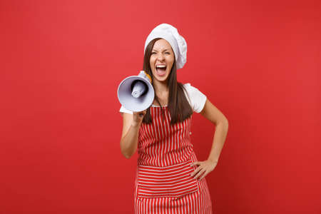 Housewife female chef cook or baker in striped apron, white t-shirt, toque chefs hat isolated on red wall background. Woman scream in megaphone, announces discounts sale. Mock up copy space concept