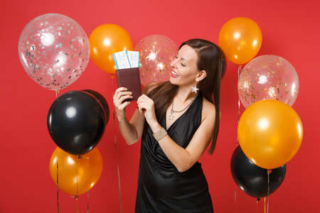 Joyful girl in black dress celebrating looking on passport boarding pass tickets in hands on bright red background air balloons. Valentine's Day, Happy New Year, birthday mockup holiday party concept