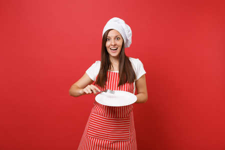 Housewife female chef cook or baker in striped apron, white t-shirt, toque chefs hat isolated on red wall background. Housekeeper woman hold empty round plate with fork. Mock up copy space concept Banque d'images