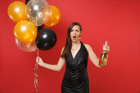 Shocked bewildered young woman in black dress holding bottle of champagne, air balloons isolated on red background. International Women's Day, Happy New Year, birthday mockup holiday party concept