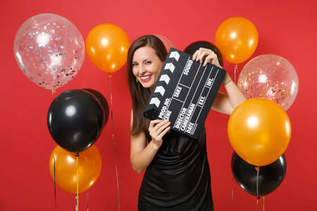 Smiling young girl in little black dress hiding behind classic black film making clapperboard on bright red background air balloon. Women's Day, Happy New Year, birthday mockup holiday party concept