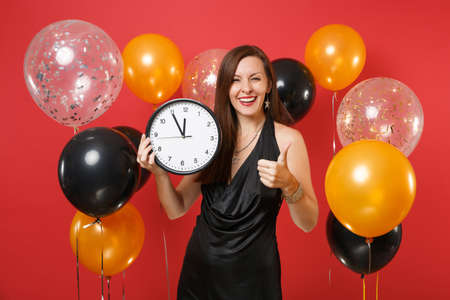 Smiling young woman in black dress celebrating holding round clock, showing thumb up isolated on red background air balloon. St. Valentine's Day, Happy New Year, birthday mockup holiday party concept Banque d'images - 114028051