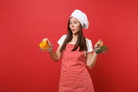 Housewife female chef cook baker in striped apron white t-shirt toque chefs hat isolated on red wall background. Woman hold yellow pepper cucumber in grocery push cart Mock up copy space concept Banco de Imagens