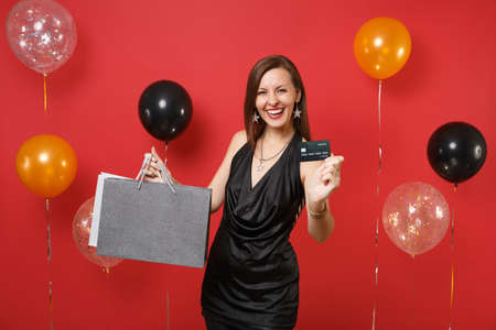 Smiling young girl in black dress holding credit card, colored packages bags with purchases after shopping on bright red background air balloon. Happy New Year, birthday mockup holiday party concept 写真素材