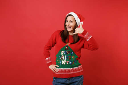 Joyful young Santa girl doing phone gesture like says: call me back with hand, fingers like talking on the telephone isolated on red background. Happy New Year 2019 celebration holiday party concept Stock fotó