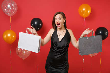 Excited girl in black dress celebrating holding multi colored packages bags with purchases after shopping on bright red background air balloons. Happy New Year, birthday mockup holiday party concept