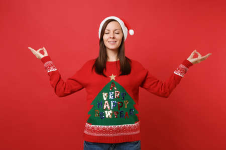 Relaxed young Santa girl with closed eyes in Christmas hat meditate spreading hands isolated on bright red wall background. Happy New Year 2019 celebration holiday party concept. Mock up copy space Stock Photo