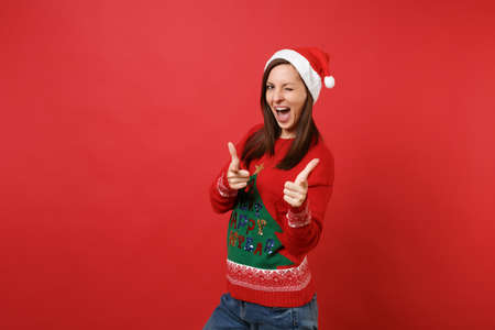 Merry young Santa girl in knitted sweater Christmas hat pointing index fingers on camera blinking isolated on red background. Happy New Year 2019 celebration holiday party concept. Mock up copy space Stock Photo