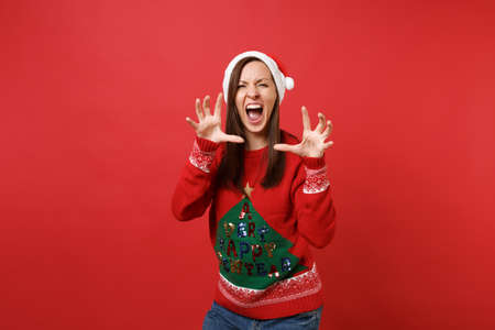 Crazy young Santa girl in Christmas hat shouting, growling like animal, making cat claws gesture isolated on red background. Happy New Year 2019 celebration holiday party concept. Mock up copy space