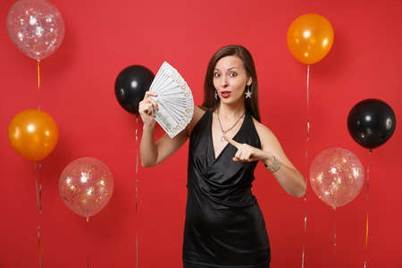 Amazed girl in black dress celebrating pointing index finger on bundle lots of dollars, cash money in hand on bright red background air balloons. Happy New Year, birthday mockup holiday party concept
