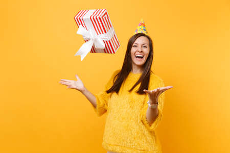 Laughing young woman in birthday party hat throwing up red box with gift present, celebrating and enjoying holiday isolated on bright yellow background. People sincere emotions, lifestyle concept