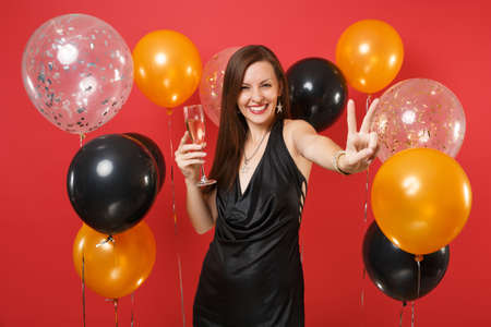 Smiling girl in black dress celebrating holding glass of champagne, showing victory sign on bright red background air balloons. Valentine's Day, Happy New Year, birthday mockup holiday party concept