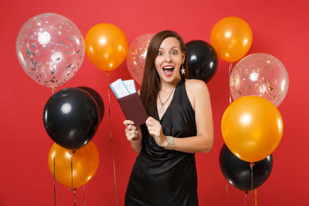 Excited girl in black dress celebrating holding passport, boarding pass tickets on bright red background air balloons. International Women's Day, Happy New Year, birthday mockup holiday party concept