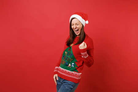 Overjoyed young Santa girl in knitted sweater Christmas hat screaming doing winner gesture isolated on bright red background. Happy New Year 2019 celebration holiday party concept. Mock up copy space