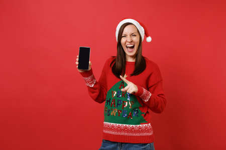 Cheerful young Santa girl screaming pointing index finger on mobile phone with blank empty screen isolated on red background. Happy New Year 2019 celebration holiday party concept. Mock up copy space Stock Photo