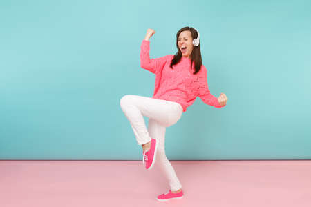 Full length portrait of happy young woman in knitted rose sweater, white pants, headphones isolated on bright pink blue pastel wall background in studio. Fashion lifestyle concept. Mock up copy space