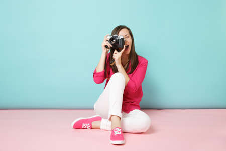Full length portrait young woman in rose shirt blouse white pants sitting on floor hold camera isolated on pink blue pastel wall background studio. Fashion lifestyle concept. Mock up copy space Banco de Imagens