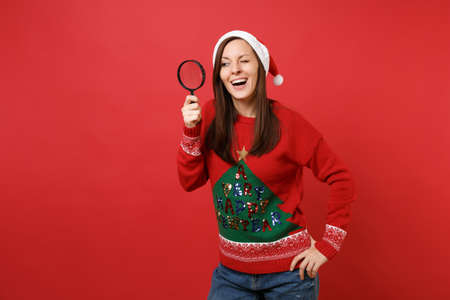 Curious young Santa girl in Christmas hat looking attentively behind magnifying glass isolated on bright red wall background. Happy New Year 2019 celebration holiday party concept. Mock up copy space