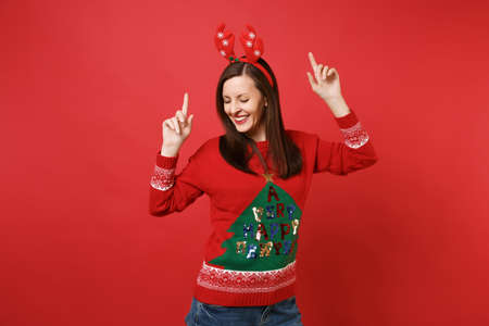 Cheerful young Santa girl in fun decorative deer horns on head dancing, pointing index fingers up isolated on red background. Happy New Year 2019 celebration holiday party concept. Mock up copy space