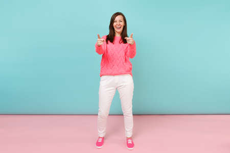 Full length portrait of smiling young woman in knitted rose sweater, white pants posing isolated on bright pink blue pastel wall background in studio. Fashion lifestyle concept. Mock up copy space Imagens