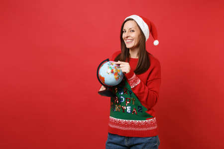 Smiling young Santa girl in knitted sweater, Christmas hat keeping finger on world globe in hands isolated on red background. Happy New Year 2019 celebration holiday party concept. Mock up copy space