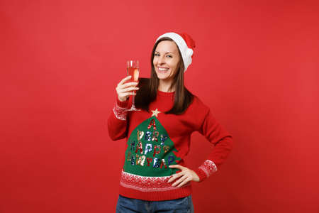 Smiling young Santa girl in knitted sweater, Christmas hat holding glass of champagne isolated on bright red wall background. Happy New Year 2019 celebration holiday party concept. Mock up copy space