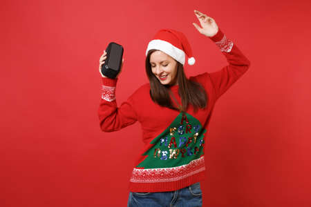 Tender young Santa girl dancing, rising hand, holding portable wireless music speaker isolated on red background. Happy New Year 2019 celebration holiday party concept. Mock up copy space Stock Photo